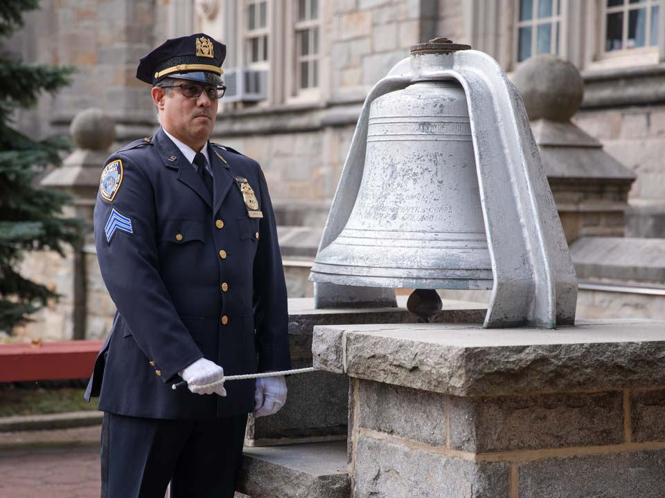 Photo of NYPD officer ringing WAVES Bell during 9/11 Remembrance Ceremony