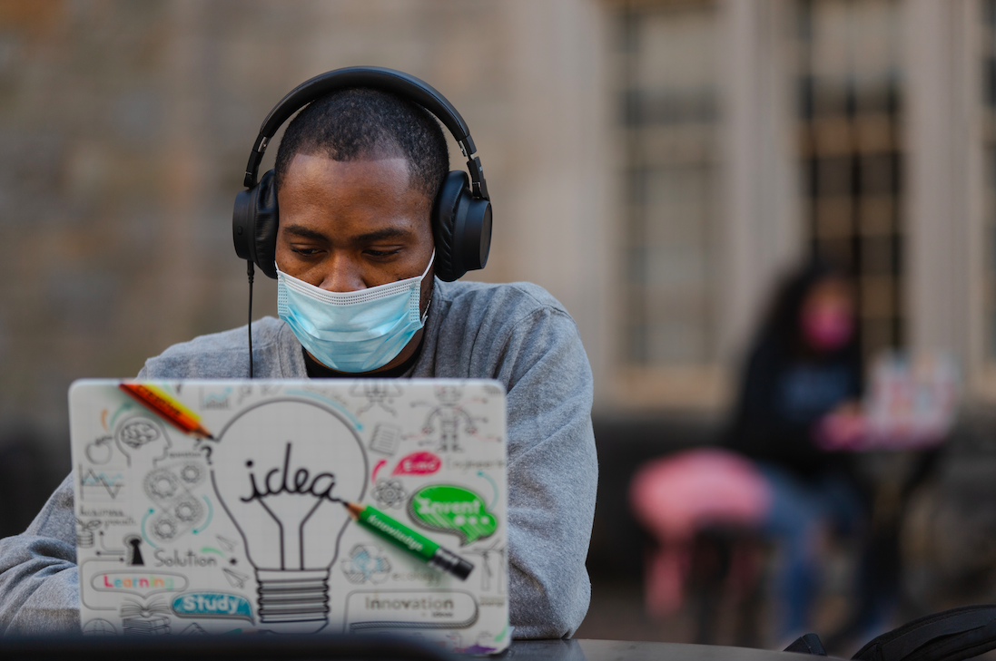 Masked man with headphones using a laptop.